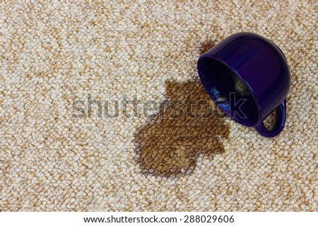 Coffee spilled from cup on carpet  - stock photo