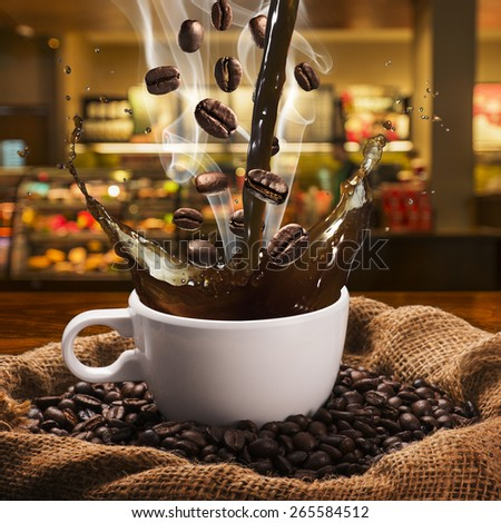 Coffee Splash from Cup With Coffee Beans. Coffee Shop in Background - stock photo