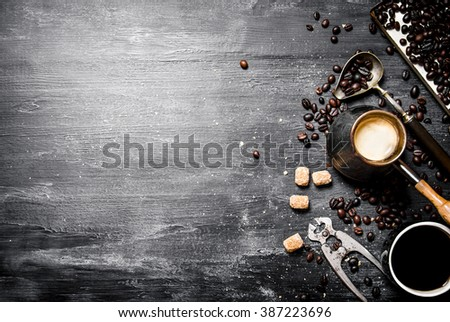 coffee style . Brewed coffee pot with sugar and coffee beans around. On a black chalkboard. - stock photo