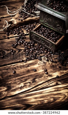 Coffee style. Coffee grinder with roasted coffee grains. On wooden background. - stock photo
