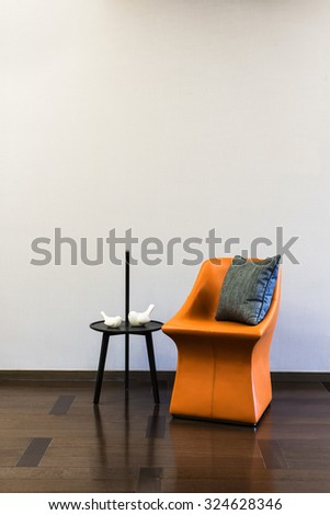 Coffee table Orange Leather chair combination in front of a plain wall - stock photo