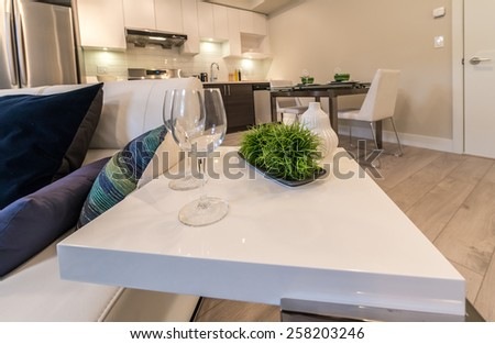 Coffee table with wine glasses and decorative table and dinning table at the back. Interior design. - stock photo