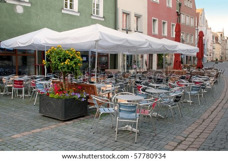 Coffee tables with umbrellas near cafe on European street, Weiden, Bavaria, Germany - stock photo