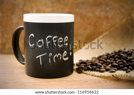 coffee time, mug with coffee beans & hessian on counter - stock photo