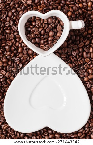 Coffee time. White cup and saucer in shape of heart on roasted coffee beans background. Top view - stock photo