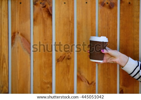 Coffee to go. Disposable cup in woman hand on background of wooden planks - stock photo