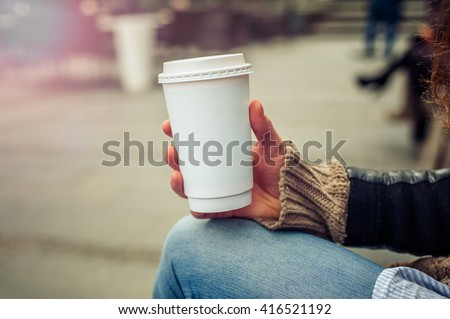 Coffee to go. Woman drinking coffe on the street. Close up - stock photo