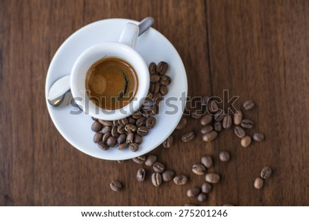 Coffee with a smile of cream and roasted beans in a white porcelain cup - stock photo