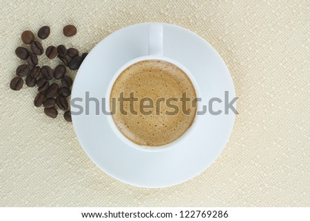 coffee with cream and coffee beans against the background of beige tablecloth - stock photo