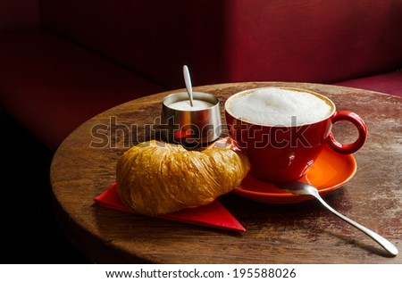 coffee with croissant and sugar bowl in a cafe - stock photo