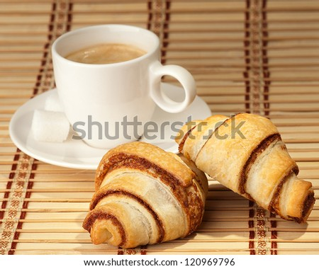 Coffee with croissant, on a bamboo tray