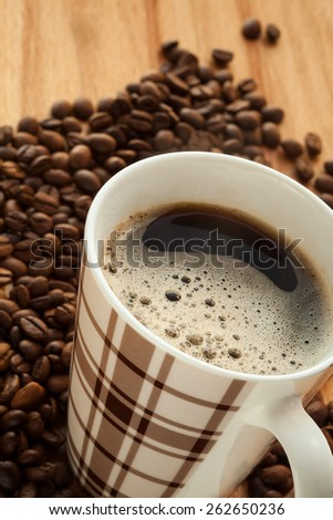 Coffee with foam and coffee beans. close