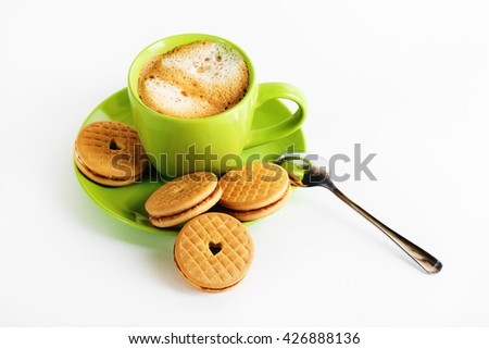 Coffee with foam in a green cup, saucer, spoon and tasty cookies. - stock photo