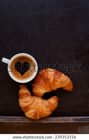 coffee with heart sign and croissant at board - stock photo