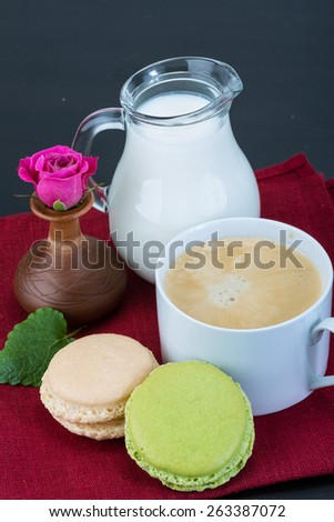 Coffee with macaroons and milk served rose
