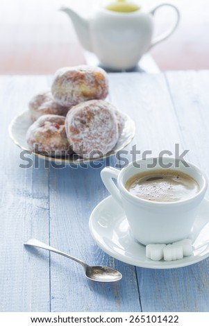 Coffee with milk and sweet dessert. Donuts with icing sugar - stock photo