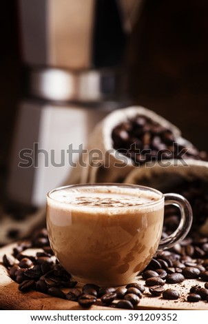 Coffee with milk, coffee maker, coffee beans, dark toned image, selective focus