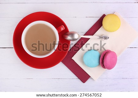 Coffee with milk. Cup of coffee and a macaroon. Colorful macaroons on the table. A Cup, a spoon and desserts. French dessert macaroon. Red Cup with saucer. A delicious Breakfast. Coffee and sweets. - stock photo