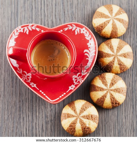 Coffeee in red cup and biscuits over wooden table, square image - stock photo