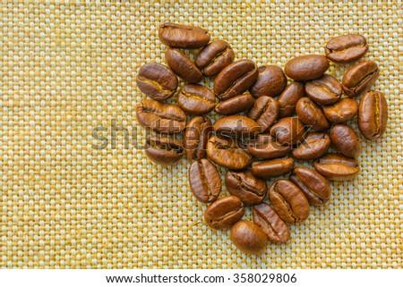 Coffees bean,heart shape on a vintage burlap - stock photo