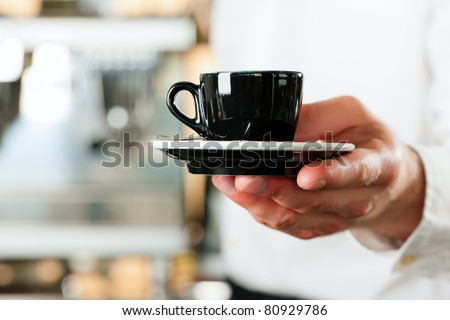 Coffeeshop - barista presents coffee or cappuccino; close-up on mug - stock photo
