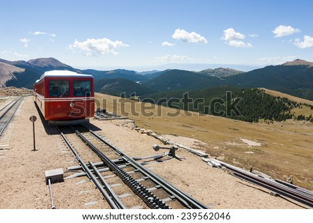 Cog Railway Tracks and a Red Train in Distance, Pikes Peak, Colorado. - stock photo