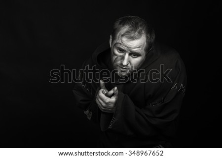 Cogent game actor faithful image of the hero on a dark background. Theater actor in the guise of a beggar. Professional theatrical makeup and costume. Game touching actor. - stock photo