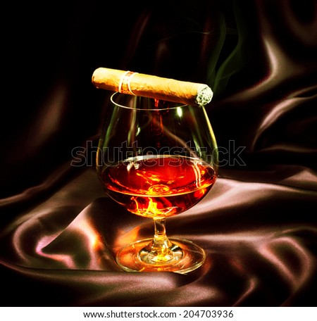Cognac and Cigar. Glass of Brandy over dark background - stock photo