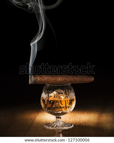 Cognac and cigar on wooden background close up - stock photo