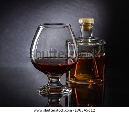 Cognac bottle and glass on the dark background. - stock photo