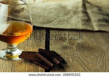 Cognac glass and chocolate horizontal selective focus copy space - stock photo