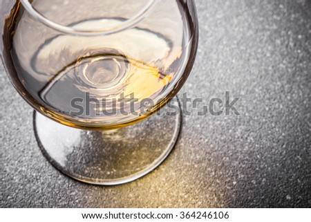 Cognac glass on black surface. - stock photo