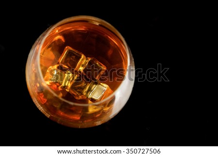 Cognac glass with ice cubes on black background - stock photo