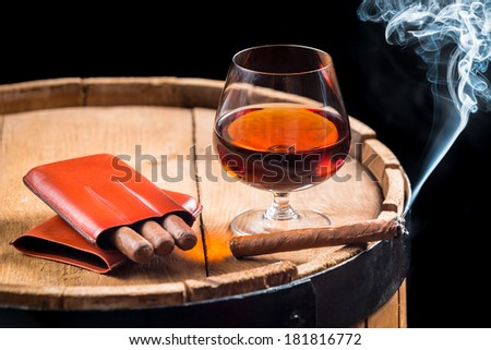 Cognac in a glass on barrel and burning cigar - stock photo