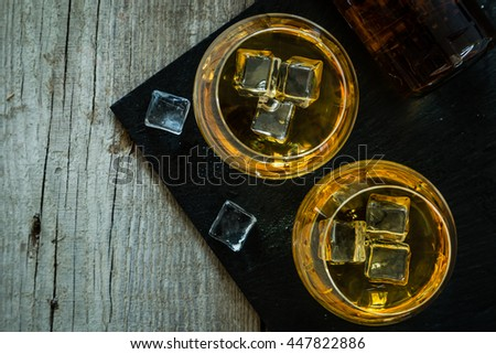Cognac in glasses on rustic backgrpund - stock photo