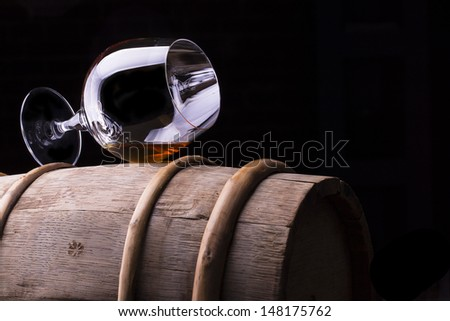 Cognac or brandy on a wooden vintage barrel with black background - stock photo
