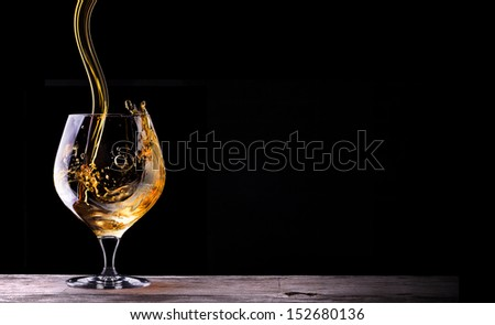 Cognac or brandy on a wooden vintage table with black background - stock photo