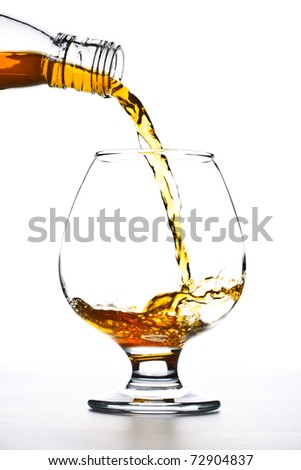 cognac pour into the glass over white background - stock photo