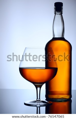 Cognac, whisky, rum, wine glass and bottle on blue background - stock photo