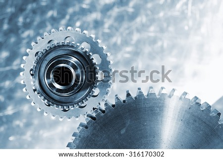 cogwheels and gears, titanium and steel against brushed aluminum, blue toning concept - stock photo