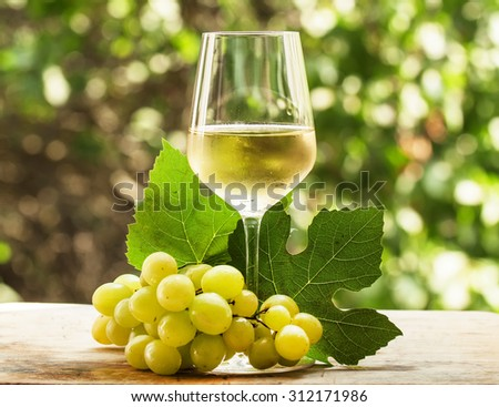 Coid white wine and green grapes on natural blurred background with bokeh, selective focus - stock photo