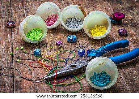 coil,beads and tools for needlework on turquoise wooden background - stock photo