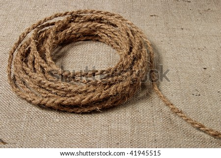 Coil of coarse rope on burlap background - stock photo
