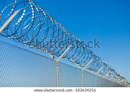 Coiled razor wire with its sharp steel barbs on top of a wire mesh perimeter fence ensuring safety and security, preventing access or the escape of prisoners, blue sky background - stock photo