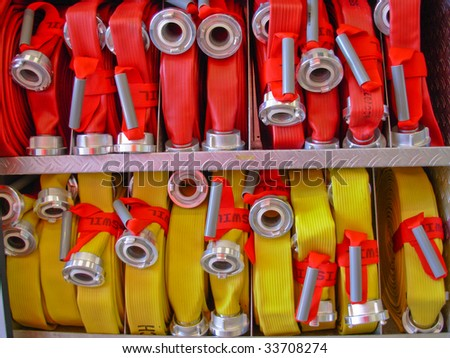 Coiled red and yellow fire hoses.