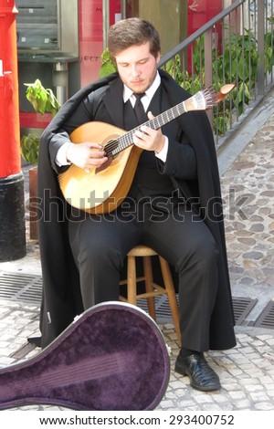 COIMBRA, PORTUGAL - CIRCA JUNE 2015: unidentified street fado guitar player in traditional costume - stock photo