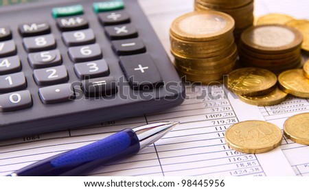 coin, a calculator, a pen on the business papers - stock photo