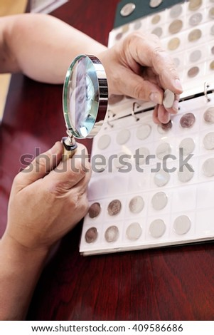 Coin collector is looking at his collection through a magnifying glass