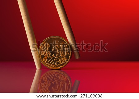 Coin held by chopstick over red background - stock photo