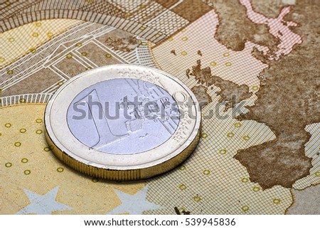 Coin one euro on the fifty euros banknote